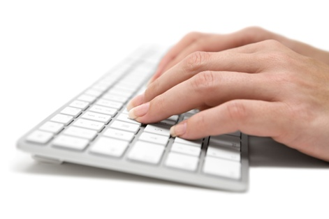 Woman typing on a modern keyboard. White background.