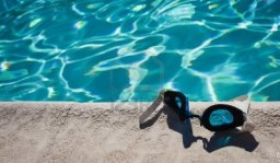 10010917-a-close-up-of-a-pair-of-swim-goggles-laying-on-the-edge-of-the-pool